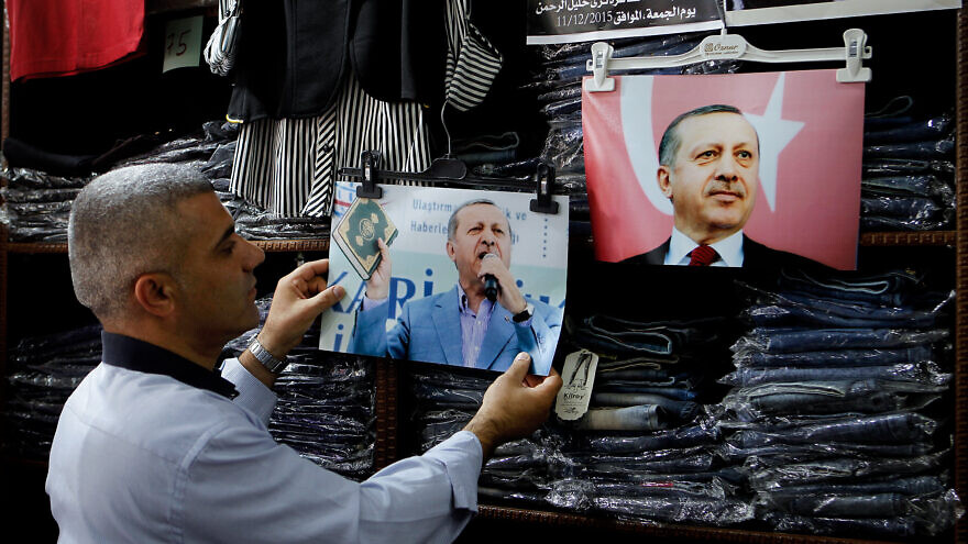A Palestinian shop owner hangs pictures of the Turkish President Recep Tayyip Erdoğan in the West Bank city of Hebron on July 20, 2016. Photo by Wisam Hashlamoun/Flash90.