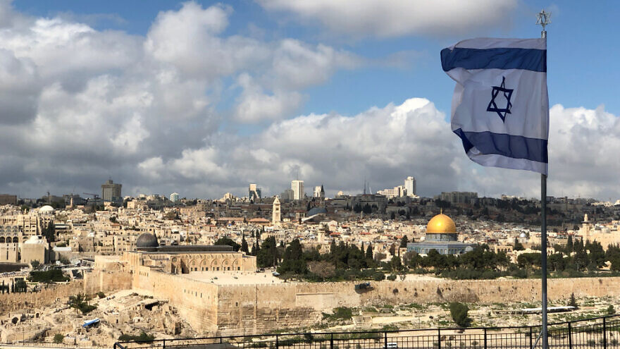A view of Jerusalem with the Israeli flag in the foreground. Credit: John Theodor/Shutterstock.