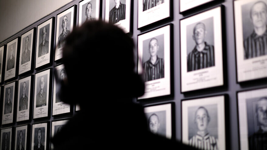 A visitor looks at photographs of camp inmates at the Auschwitz-Birkenau Museum and Memorial in Oswiecim, Poland. Credit: Desi H. Sitorus/Shutterstock.