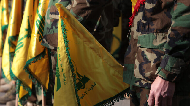 Hezbollah fighters holding the terror group's flags. Credit: nsf2019/Shutterstock.