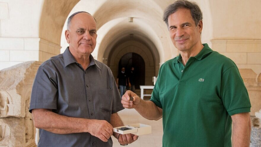 Israeli astronaut Eytan Stibbe holding the ancient coin. Credit: Israel Antiquities Authority/Facebook.