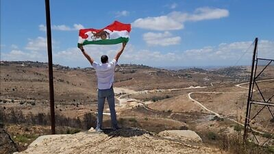 """Ahmad Batebi, an Iranian non-Jewish activist and journalist waiving the """"Sun and Lion"""" Iranian flag that was used during the Pahlavy dynasty, in Israel. Credit: Courtesy."""