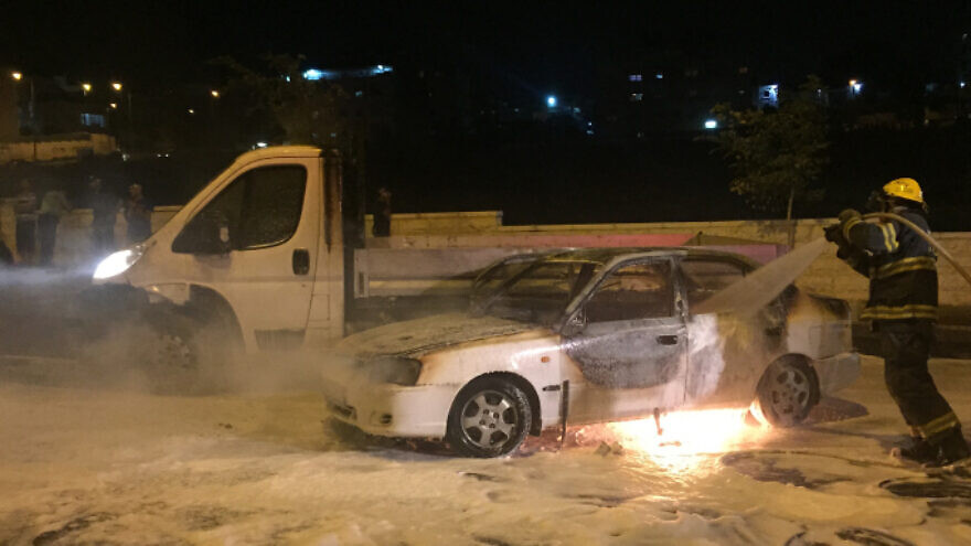 Firefighters extinguish a fire caused by a firebombing near the Arab neighborhood of Beit Hanina in eastern Jerusalem. Two people were injured in the attack, one woman was evacuated to Hadassah Medical center with severe burns. August 3, 2015. Photo by Sliman Khader/Flash90.