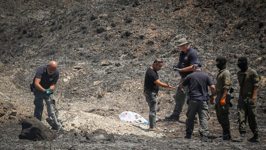 Israeli security at the scene of where a missile fired from Lebanon, into northern Israel, hit in an open field, near the city of Kiryat Shmona, Aug. 4, 2021. Photo by David Cohen/Flash90.