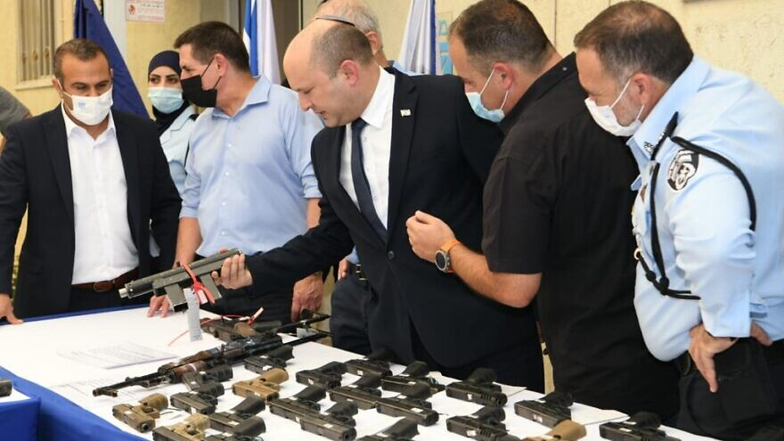 """Israeli Prime Minister Naftali Bennett inspects illegal weapons seized during the Israel Police's """"Operation Sword Strike"""" in the country's Arab sector, Aug. 11, 2021. Photo by Amos Ben-Gershom/GPO."""