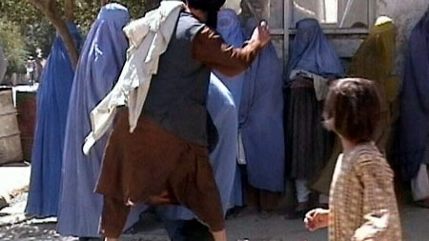 A member of the Taliban's religious police beats an Afghan woman in Kabul on Aug. 26, 2001. The footage, filmed by the Revolutionary Association of the Women of Afghanistan, can be seen at: pz.rawa.org/rawasongs/movie/beating.mpg. Credit: Wikipedia.