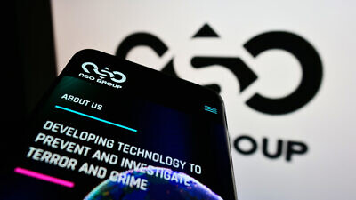 Cellphone with webpage of Israeli technology company NSO Group Technologies Ltd. on screen in front of logo. Credit: T. Schneider/Shutterstock.