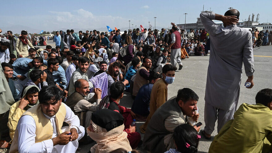 Afghanis crowd the airport in Kabul after U.S. troops get ready to withdraw and the Taliban wait to take over the country, Aug 18, 2021. Credit: John Smith 2021/Shutterstock.