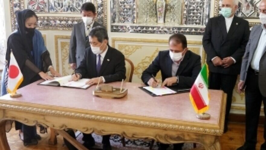 Japanese Ambassador to Iran Kazutoshi Aikawa and Mahdi Mirashrafi, president of Iran's Customs Administration and deputy finance minister, sign a customs agreement in Tehran on Aug. 22, 2021, in the presence of Japanese Foreign Minister Toshimitsu Motegi (top left) and his Iranian counterpart (standing, far right) Mohammed Javad Zarif. Credit: Foreign Ministry of Japan.