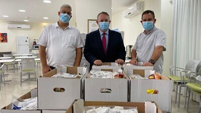 Displaying Rosh Hashanah care packages are (from left) Deputy Mayor of Kfar Saba Oren Cohen; Jewish Agency chairman of the executive and chairman of the executive of the World Zionist Organization Yaakov Hagoel; and, senior vice president of Amigour Erez Shani, September 2021. Credit: Amigour.