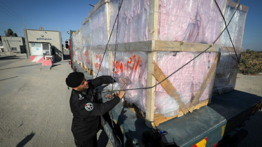 A Palestinian policeman inspects a truckload of textiles at the Kerem Shalom crossing in the Gaza Strip, June 21, 2021. Photo by Abed Rahim Khatib/Flash90.