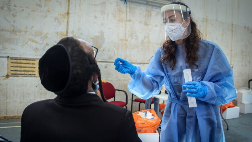 An Israeli health worker takes COVID-19 test samples in Tzfat on Aug. 31, 2021. Photo by David Cohen/Flash90.