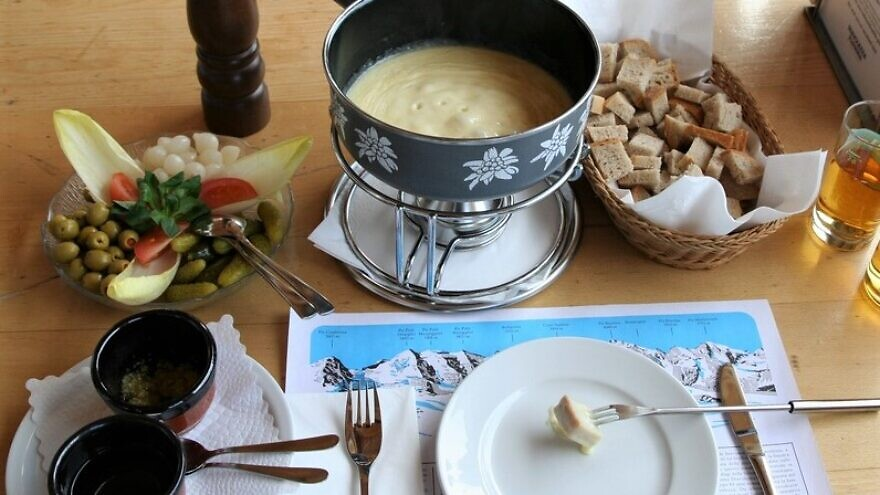 A full cheese fondue set in Switzerland. Apart from pieces of bread to dip into the melted cheese, it comes with side servings of kirsch, raw garlic, olives, pickled gherkins and baby onions. Credit: Wikimedia Commons.