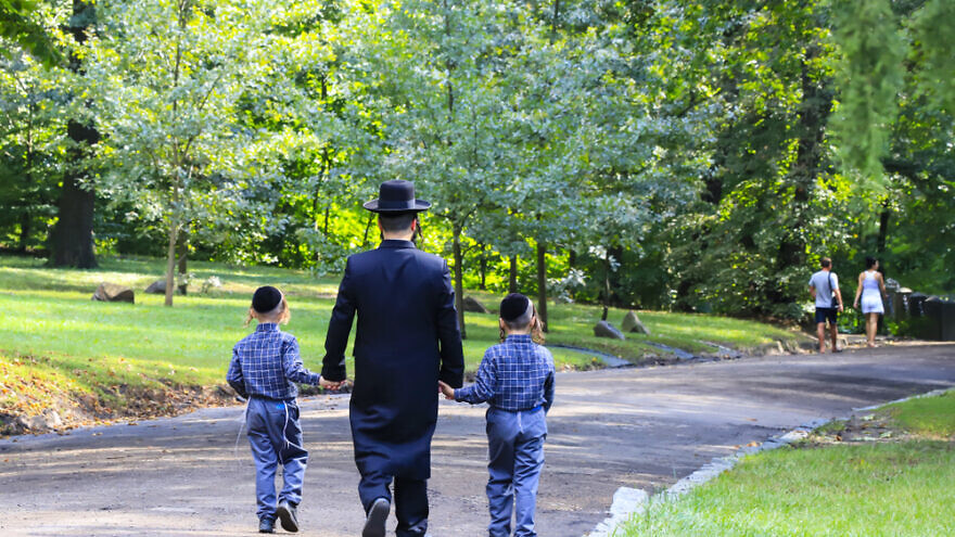 A Jewish man and his children walking in a park. Credit: Shutterstock.