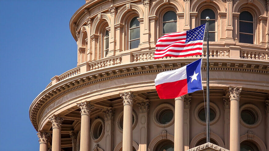 U.S. and Texas state flags flying on the dome of the Texas State Capitol building in Austin. Credit: CrackerClips Stock Media/Shutterstock.