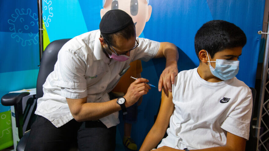 A young Israeli receives a booster shot of the Pfizer/BioNTech COVID-19 vaccine, Sept. 20, 2021. Photo by Olivier Fitoussi/Flash90.